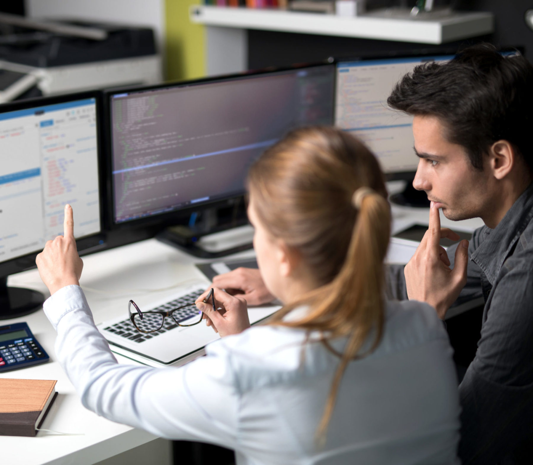 two individuals reviewing website code on multiple computer screens