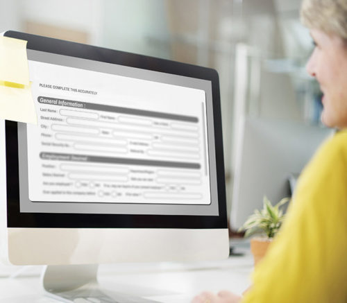 Elderly lady filling out a form on a government website