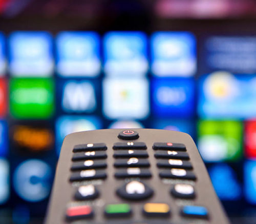 universal remote control with blurred smart tv in background