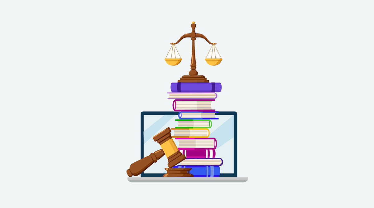 Laptop with a pile of books on it, topped by the scales of justice. In the foreground is a judge's gavel