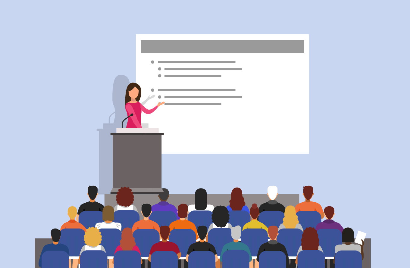 A woman behind a podium, giving a presentation to a large audience
